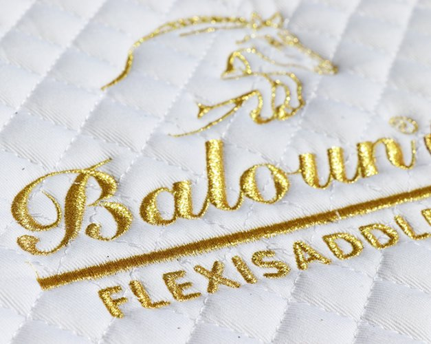 Detail of gold embroidery on saddle pad Baloun®. Emdroidered with gold metal thread